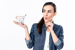 Cunning woman holding shopping cart model on palm. Portrait of cunning woman holding shopping cart model on palm Stock Photography