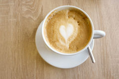 A cuo of cappuccino on a wooden table. A white cup of cuppuccino on a wooden table Royalty Free Stock Images