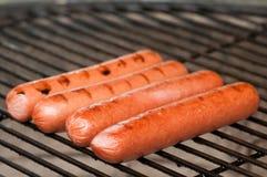 Cuocere i hot dog alla griglia Fotografia Stock Libera da Diritti