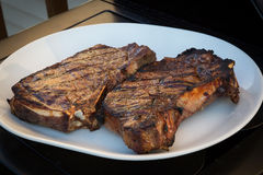 Cuocere le bistecche alla griglia Fotografie Stock Libere da Diritti