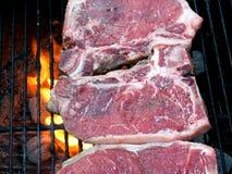 Cuocere le bistecche alla griglia di bistecca con l'osso Immagini Stock