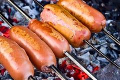 Cuocere le salsiccie alla griglia fotografie stock