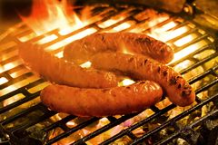 Cuocere le salsiccie alla griglia su una griglia del carbone di legna Fotografia Stock
