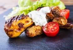 cuocere Pollo cotto Piedini di pollo cotti Coscie di pollo arrostite, lattuga e pomodori ciliegia Cucina tradizionale Mediterra Fotografie Stock