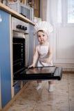 Cuochi del cuoco unico del bambino nell'alimento del forno Immagine Stock