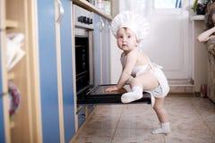 Cuochi del cuoco unico del bambino nell'alimento del forno Fotografie Stock