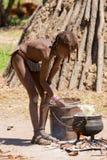 Cuochi del ragazzo di Himba per pranzo Fotografia Stock Libera da Diritti