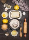 Cuocia gli ingredienti e gli strumenti per la produzione di pasta del biscotto o del dolce del limone su fondo scuro, vista super Fotografie Stock