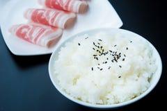 Cuocia a vapore il riso e faccia scorrere la carne di maiale cruda sulla tavola Fotografie Stock Libere da Diritti