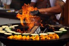 Cuoco che cucina le verdure arrostite con il pesce fotografie stock libere da diritti