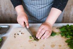 Cuoco che taglia le erbe a pezzi verdi sullo scrittorio di legno Immagini Stock