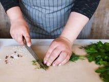 Cuoco che taglia le piante aromatiche a pezzi sul tagliere di legno Immagini Stock
