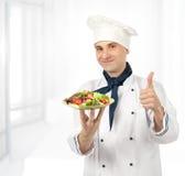 Cuoco con l'insalata sana delle verdure fotografia stock
