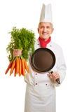 Cuoco del cuoco unico con la pentola ed il mazzo di carote Immagini Stock