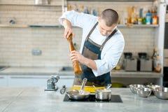 Cuoco del cuoco unico che sta e che cucina in padella sulla cucina fotografia stock