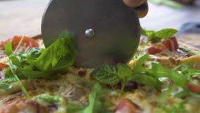 Cuoco del cuoco unico che taglia pizza con il coltello del rullo sulla tavola di legno in pizzeria Fine sul pizzaillo che taglia  stock footage