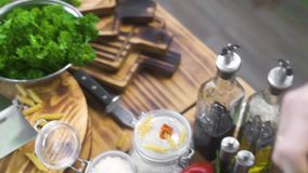 Cuoco del cuoco unico che taglia prezzemolo verde sul bordo di legno al tavolo da cucina Cuoco del cuoco unico che taglia le erbe stock footage