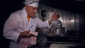 Cuoco del cuoco unico in un cappello bianco dei cuochi e del grembiule sugli odori odoranti di una cucina del pasto fotografie stock libere da diritti