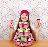 Cuoco della bambina con il dessert delizioso dei muffin sulla tavola Immagine Stock