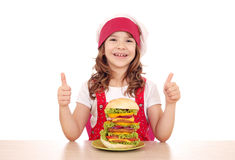 Cuoco della bambina con il grandi hamburger e pollici su Fotografia Stock Libera da Diritti