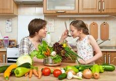 Cuoco della figlia e della madre e minestra di gusto dalle verdure Interno domestico della cucina Genitore e bambino, donna e rag immagini stock