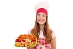 Cuoco della ragazza con le pepite di pollo e gli alimenti a rapida preparazione delle patate fritte immagini stock