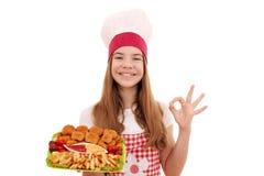 Cuoco della ragazza con le pepite di pollo ed il segno della mano di approvazione fotografia stock