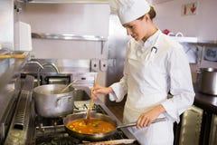 Cuoco femminile concentrato che prepara alimento in cucina Fotografia Stock