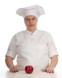 Cuoco femminile grasso serio con la mela rossa Fotografia Stock Libera da Diritti