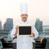 Cuoco maschio felice del cuoco unico che tiene il bordo in bianco del menu Fotografia Stock Libera da Diritti