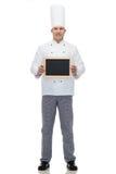 Cuoco maschio felice del cuoco unico che tiene il bordo in bianco del menu Immagine Stock