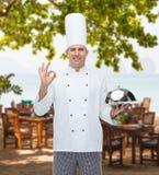 Cuoco maschio felice del cuoco unico con la campana di vetro che mostra segno giusto Immagine Stock Libera da Diritti