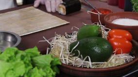 Cuoco pronto a preparare i rotoli di sushi, ortaggi freschi sulla tavola stock footage