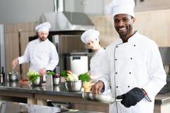Cuoco unico afroamericano che cucina dal suo immagini stock