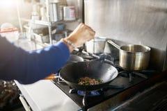 Cuoco unico in alimento del condimento della cucina del ristorante in wok caldo della padella fotografia stock