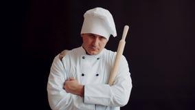 Cuoco unico arrabbiato contrariato con il matterello nel vestito bianco della cucina sul fondo nero della parete idea di concetto video d archivio