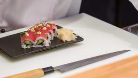 Cuoco unico asiatico che dà l'ultima volta tocco per i rotoli di sushi stock footage