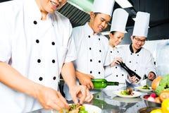 Cuoco unico asiatico nella cottura della cucina del ristorante Immagini Stock Libere da Diritti