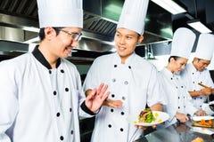 Cuoco unico asiatico nella cottura della cucina del ristorante Fotografia Stock Libera da Diritti