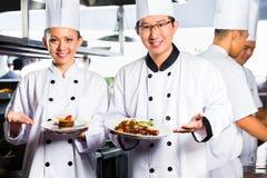 Cuoco unico asiatico nella cottura della cucina del ristorante fotografie stock libere da diritti