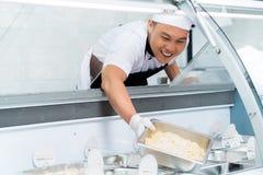 Cuoco unico asiatico sorridente che riempie un contatore dell'esposizione fotografia stock