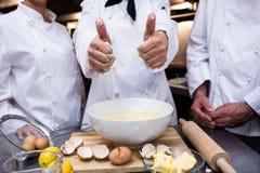 Cuoco unico capo che mostra i pollici su mentre preparando pasta Immagini Stock