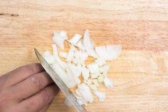 Cuoco unico che affetta cipolla su vasto di legno fotografia stock libera da diritti