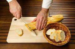 Cuoco unico che affetta pane, particolare delle mani Fotografia Stock