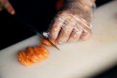 Cuoco unico che affetta salmone Immagine Stock