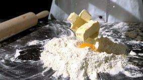 Cuoco unico che aggiunge burro all'uovo ed alla farina crudi sulla superficie del nero archivi video