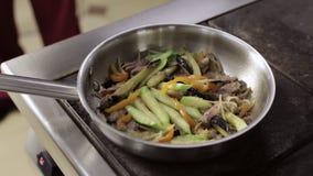 Cuoco unico che aggiunge olio d'oliva con aglio alla padella con le verdure archivi video