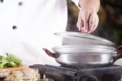Cuoco unico che apre il coperchio del vaso prima della cottura della tagliatella Fotografie Stock Libere da Diritti