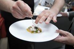 Cuoco unico che cucina alimento con il caviale ed il gamberetto per il partito di cena Fotografia Stock