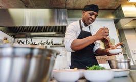 Cuoco unico che cucina alimento nella cucina del ristorante fotografia stock